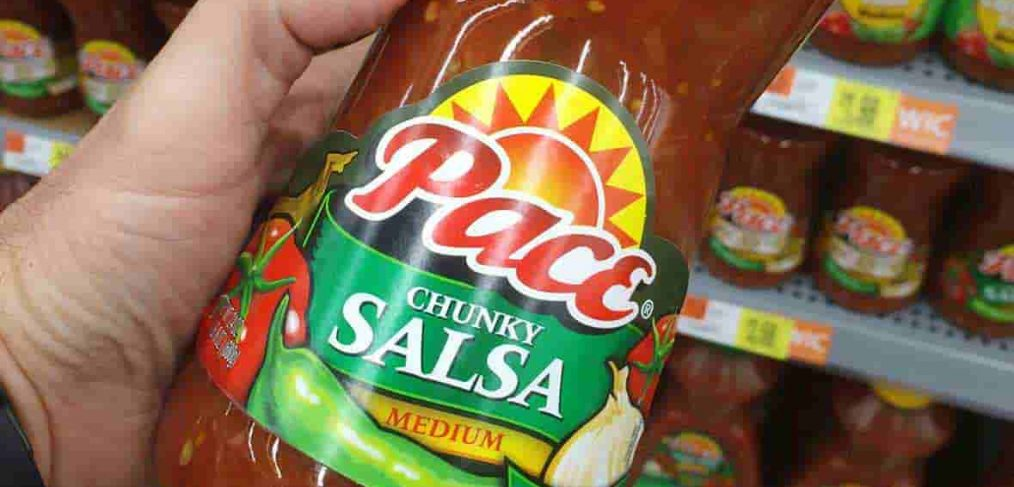 man holding bottle of pace brand salsa